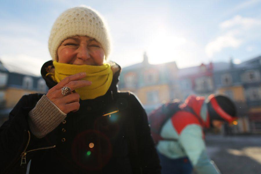 Woman wearing a hat laughing at ski resort