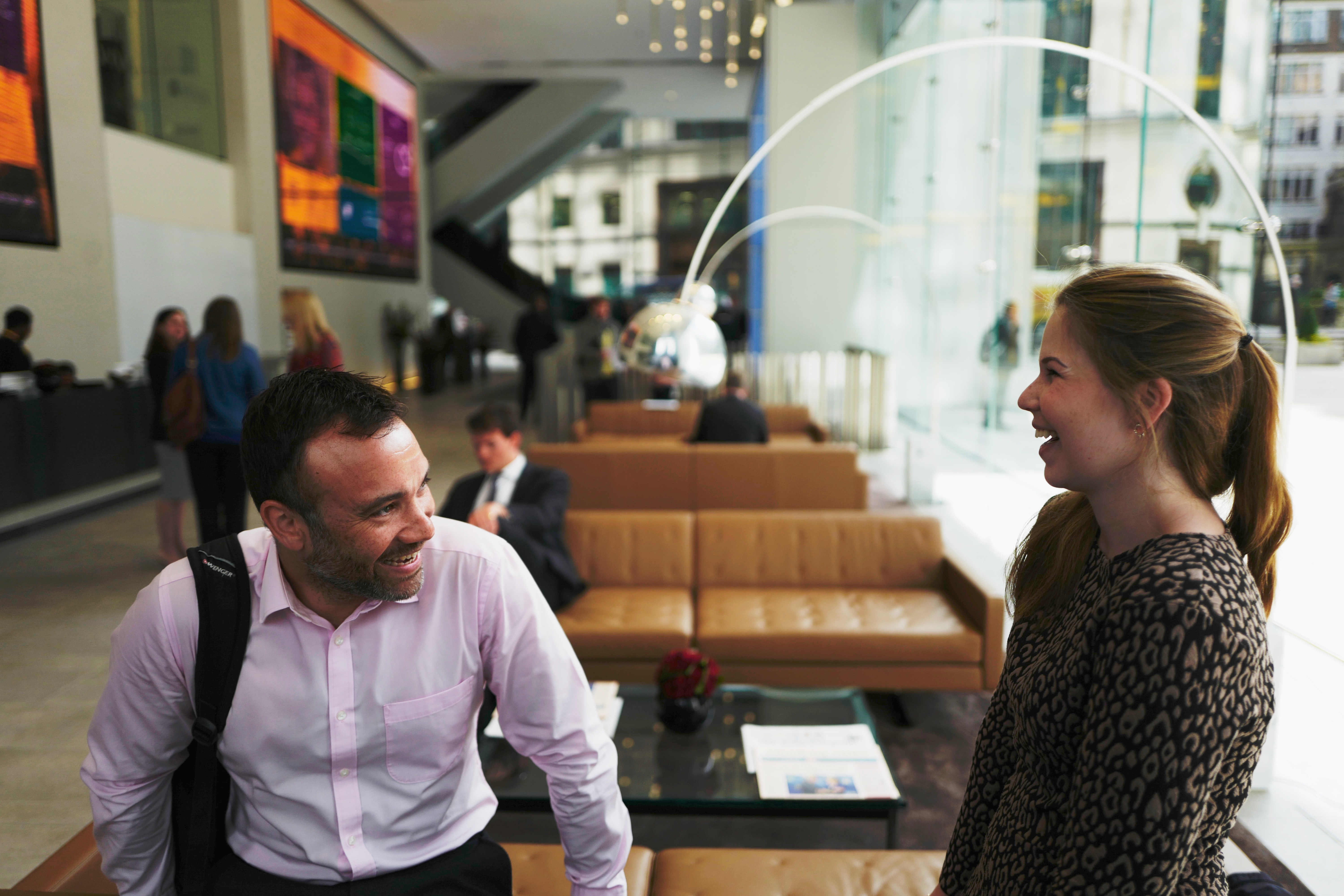 Man and woman laughing in Aviva office reception in London