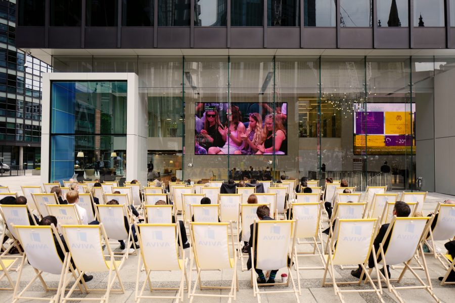 Lots of employees on Aviva branded deck chairs watching a large TV screen