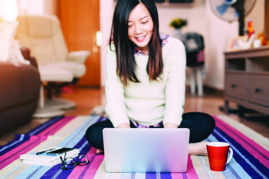 Woman working on laptop, sat on a colourful rug in living room