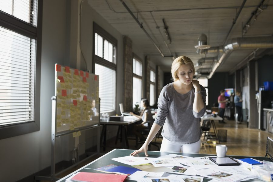 Woman looking over creative work spread over desk