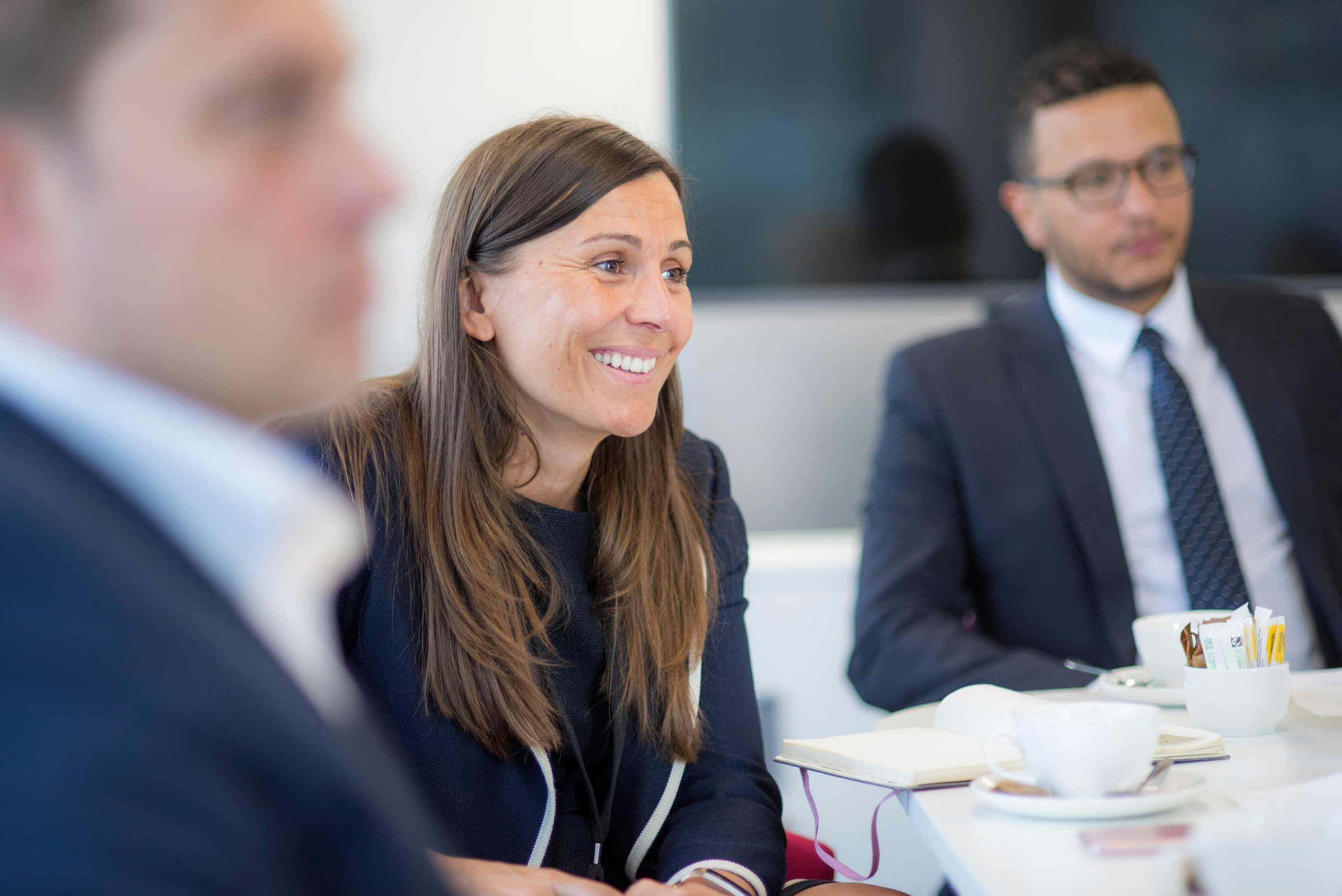 Long-haired woman smiling in a meeting environment
