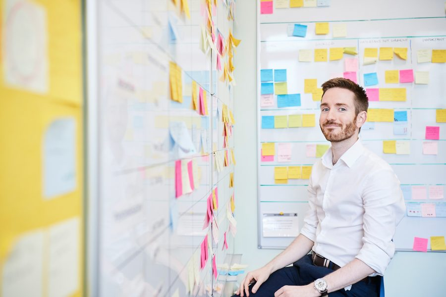 Man smiling to camera sitting in a room with whiteboards covering in sticky notes