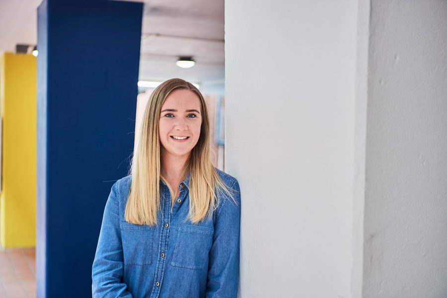 Young woman in denim shirt leaning against a wall in an office smiling to camera