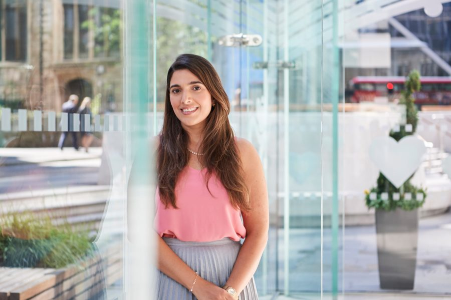 Young woman smiling to camera leaning against window in glass atrium at St Helen's, London