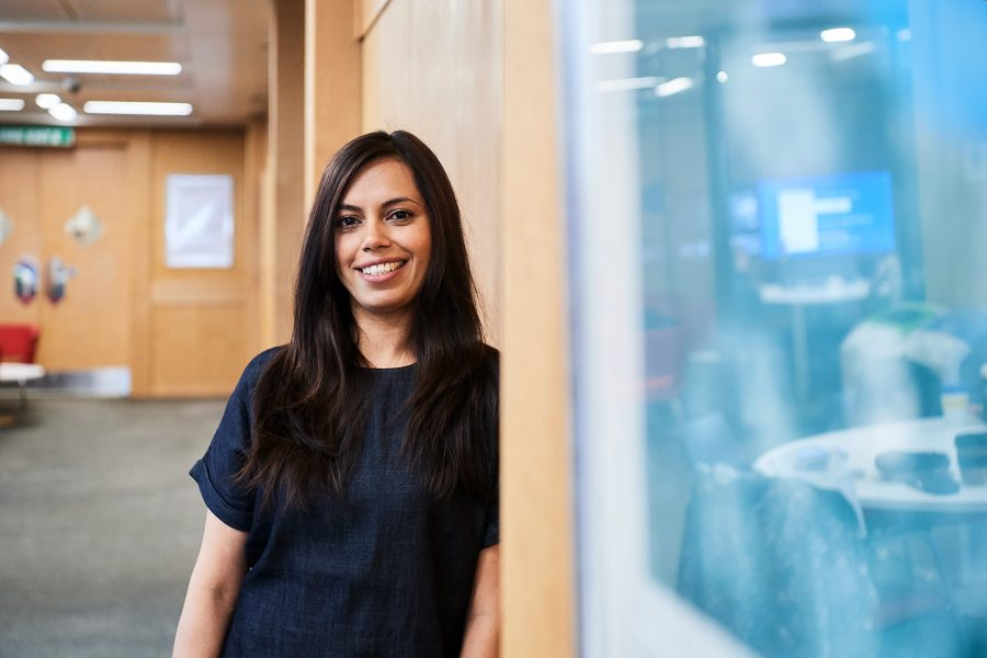 Woman smiling to camera leaning against wall in an office environment