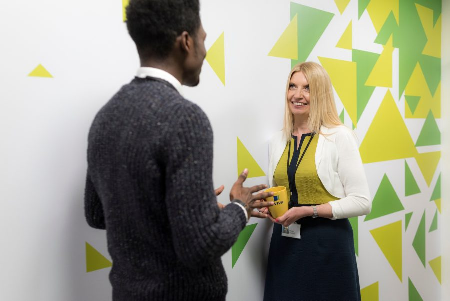 Man and woman talking against a wall in the Aviva office