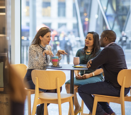 Three colleagues at a table having a discussion over a coffee