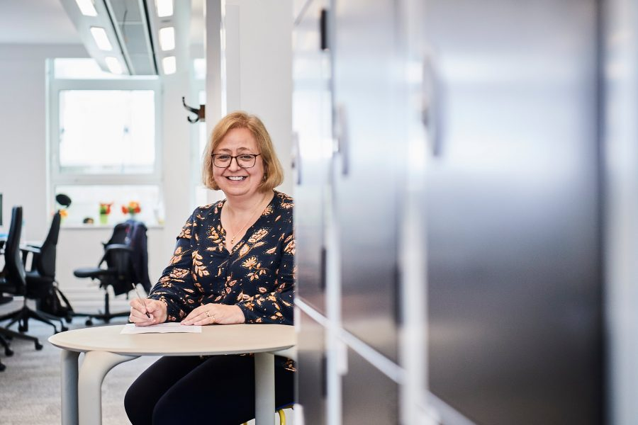 Woman smiling at camera whilst sitting at a table close to lockers in office environment