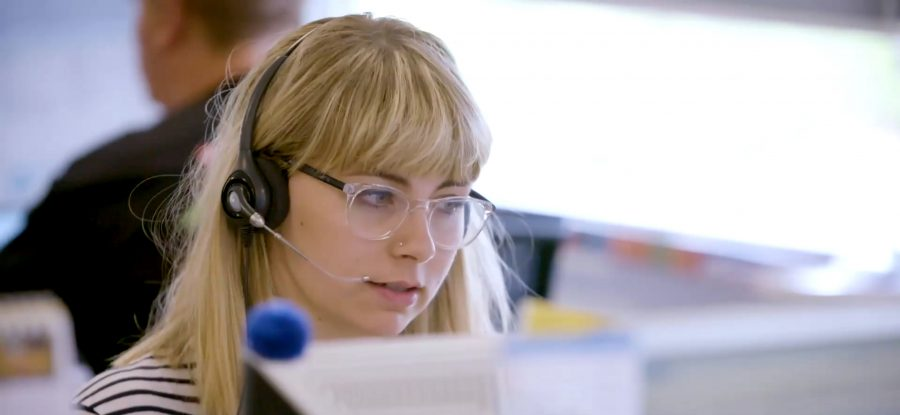 Woman wearing headset working on computer