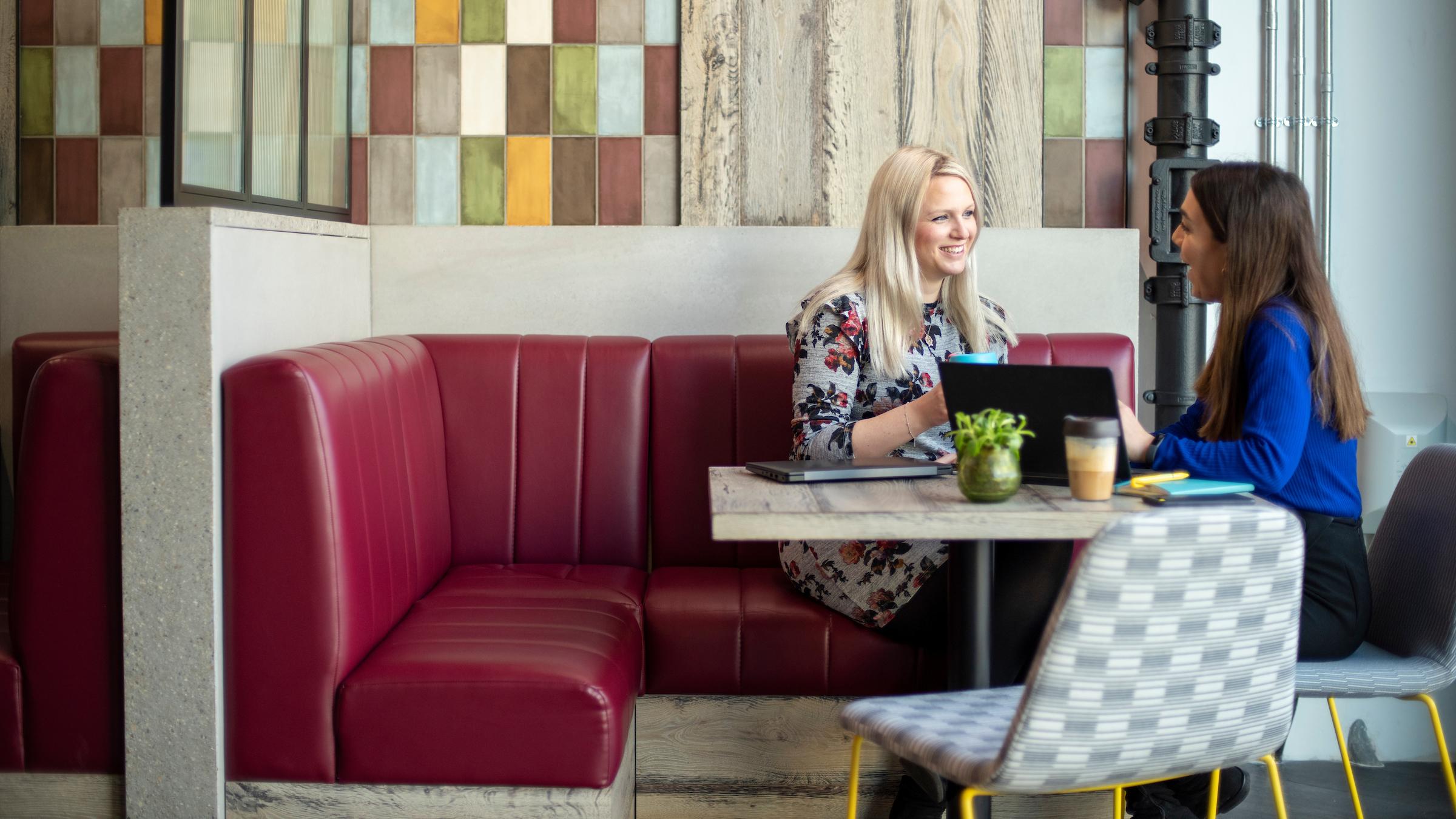 Two women in an informal meeting in a breakout area in a modern office environment