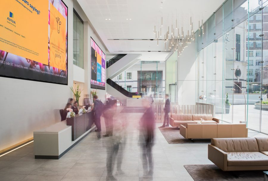 Blurred people in the foreground of a grand shot of St Helen's, London atrium and reception
