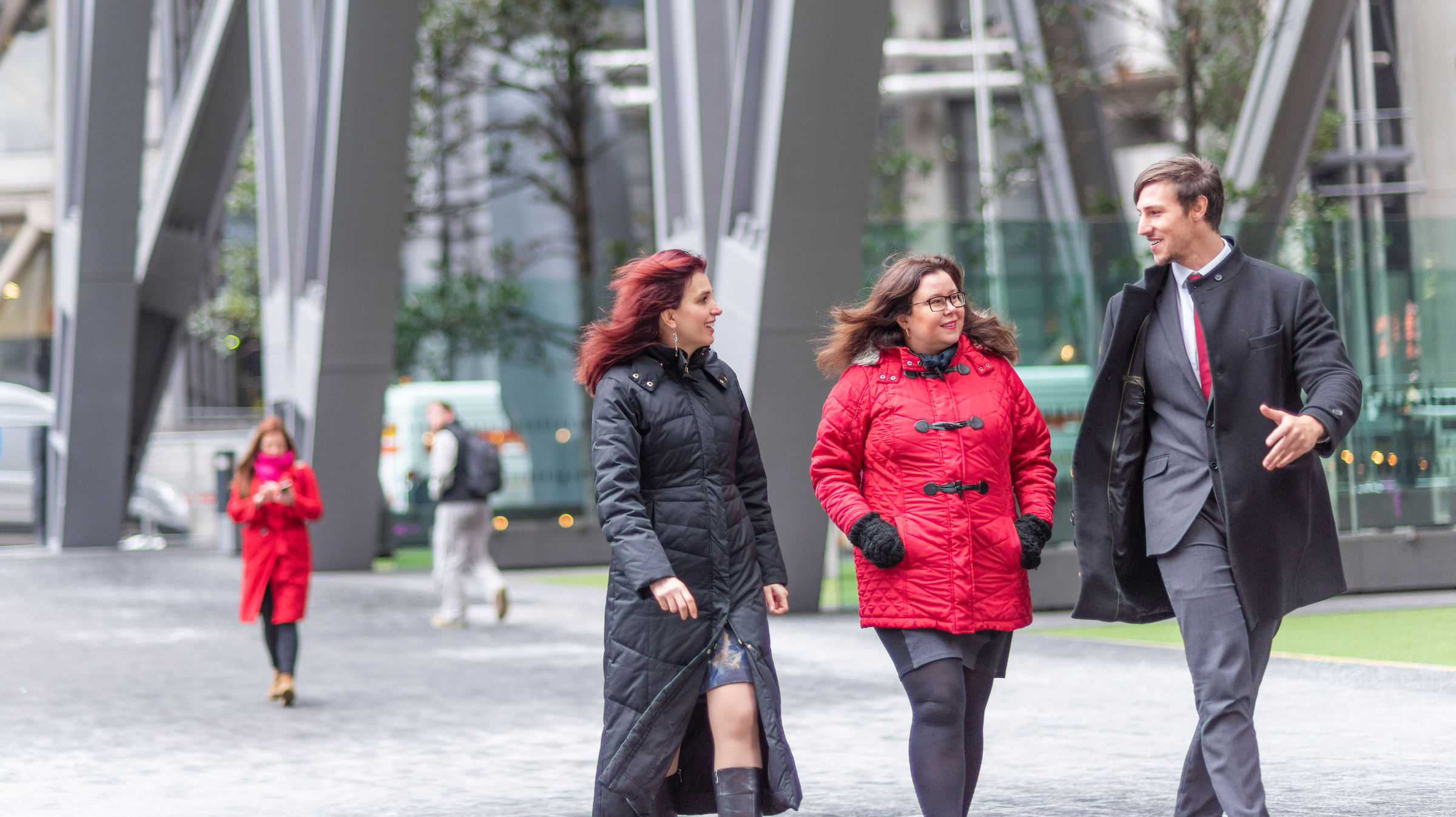Three colleagues (two female, one male) walking across a city square, wrapped up in winter coats