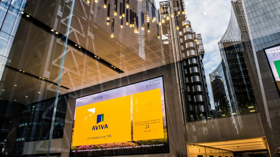 Reflection of the London skyline in the St Helen's office window, view of large digital screen with Aviva branding on inside