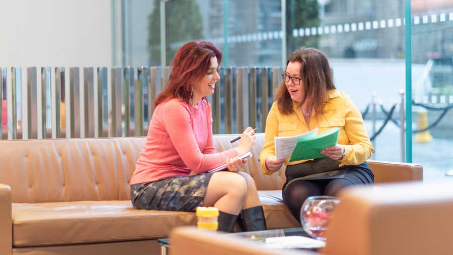 Two women in brightly coloured jumpers smiling looking at paperwork sat on a sofa