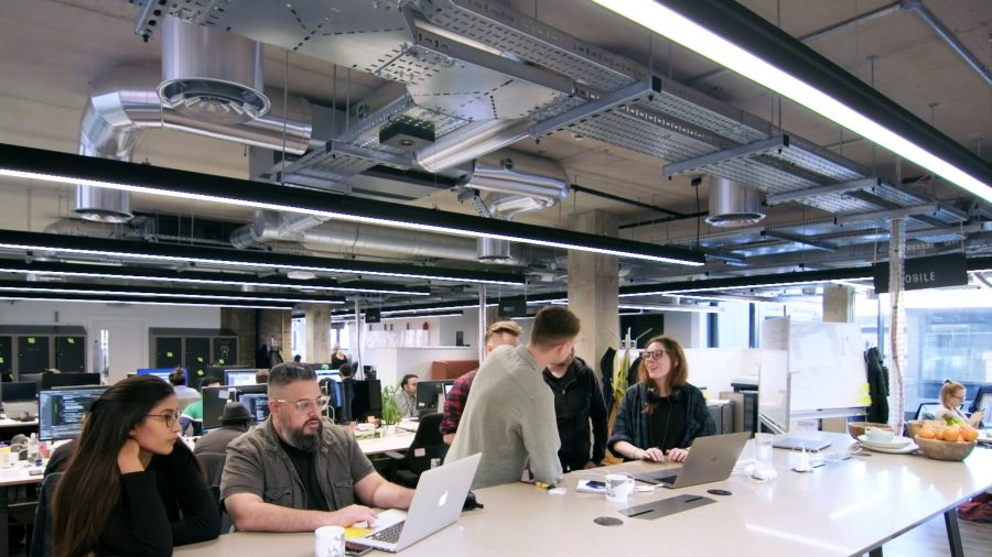 Colleagues interacting in a modern, open plan office