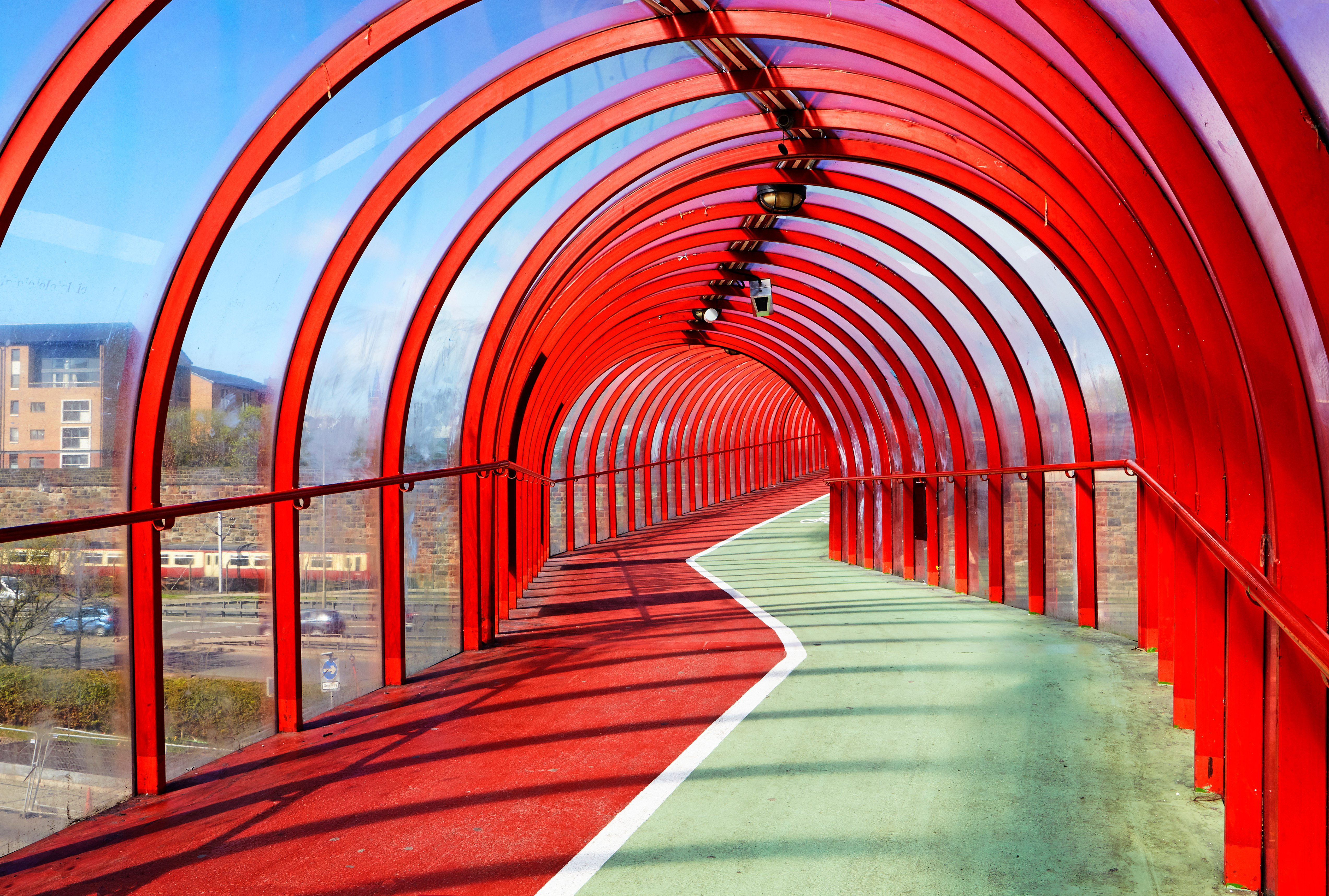 View from inside an enclosed tunnel consisting of red struts and clear panels that carries pedestrians and cyclists in Glasgow