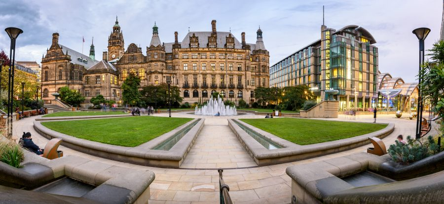 Wide shot of both old and modern buildings around a fountain in central Sheffield