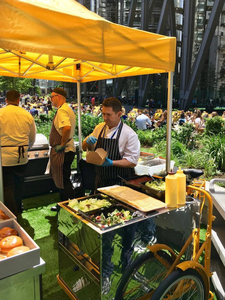 Street food stall with chefs at work, in front of Aviva London headquarters on a warm sunny day